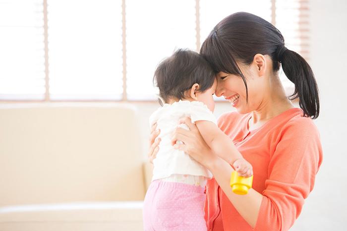 赤ちゃんとおでこをあわせる母親